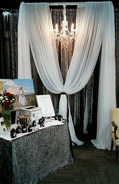 Moments In Time Wedding & Event Rentals ~ 10' H x 10' W P&D dressed with black mirror organza, white sheers, crystal curtains, chandelier, black velvet ties. Montana Association of Wedding Professionals booth at Holiday Inn Bridal Fair 2016. Please reach us at 406.208.9549 for rental info. Uses: ceremony altar, cake table, head table backdrops.