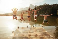Young friends jumping into lake from a jetty by jacoblund. Portrait of young friends jumping from jetty into lake. Friends in mid air on a sunny day at the lake.#lake, #jetty, #jacoblund, #Young