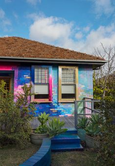 Vibrant abstract exterior mural that covers a residential home with a bright color palette of mostly pink, blue and metallic. Pops of color highlight the bricks and contrast with the garden foliage. Brick Wall Background, Watercolor Wallpaper, Happy House, Home Decor Furniture, My New Room, Exterior Paint, Paint Designs, My Dream Home, House Colors