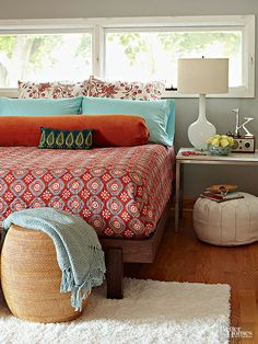 A sleek, modern bed frame and an airy bedside table make the most of this small master bedroom without weighing down the space. A complementary color palette of aqua blue and fiery orange forces the decor to remain simple, while various fabrics and patterns add punch. What we love: The bed's placement in front of the window maximizes limited square footage. Don't be afraid to place your bed in front of a window, especially if it will create more room for other essentials, such as dressers…