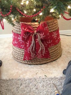 Christmas Tree Base: Lowes-large plastic garden pot, cut bottom off and turn it upside down.   3/4 inch rope, I used 60 feet exactly.   In the same isle of the rope you'll fine the brown string I used in the bow.   Hobby lobby: I found this cute sweater ribbon and I used a whole bag of hot glue. That rope isn't going anywhere ;)