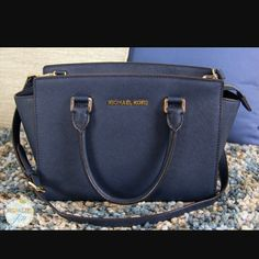 Michael kors navy selma bag-large Saffiano leather bag with metal studs on bottom to protect the leather if you keep it on the floor. Comes with both long and short handles, former of which is detachable. Interior pockets and a zipped pocket. Also has a good inside the zip pocket that you can use to secure your wallet (if your wallet also has a clasp). Light ink stain on inside only. Michael Kors Bags