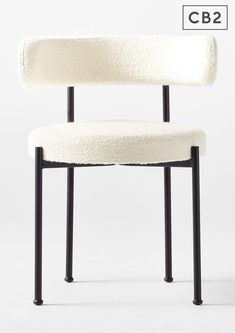 Steel tube with matte black finish frames a modern, Italian-made dining chair. Textural ivory boucle wraps the curved back and round seat in luxe contrast. CB2 exclusive.