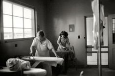 """March 1940. """"Ironing room at FSA migratory labor camp at Sinton, Texas."""" 35mm negative by Russell Lee for the Farm Security Administration"""