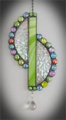 "Shades of Spring : Iridescent half circles are brought together with a flash of lime green pearl opal opaque glass.  Enhanced with shades of spring in glass marbles and adorned by a 30m Egyptian Matrix cut crystal that will bring the outdoors in with rainbows of color.  Measures 6.5"" x 12"""