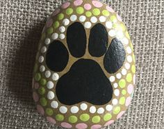 This stone is hand painted and designed by me. i used acrylic paints and varnished to a glossy finish. Length: 2.5 in Width: 2 in. Height: 3/4 in. Weight: 1/2 in.