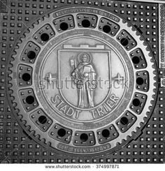 Trier, Germany - July 14, 2011: Grayscale photo of a manhole cover featuring the coat of arms of the city of Trier situated on the banks of the Moselle river. Trier may be the oldest city in Germany.