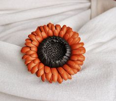 Gerberas, these daisy-like flowers in an array of fantastic colours are a simple statement of happiness. This orange gerbera is a piece from my colourful Indian Summer collection. If you are a fan of bold colours you will surely like this attractive tangerine orange flower with a chocolate brown middle. It makes a perfect little gift for your friend or sister who appreciate and love to wear unique handmade designs. It can be pinned anywhere and works well as a shawl pin. This bright flower…