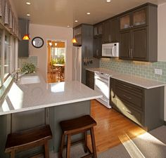 Dark cabinets, backsplash, and white appliances