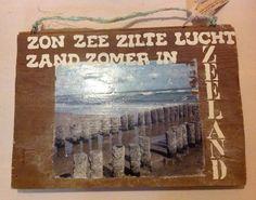 Made-by-An. Oude vloerplank met fotoprint op hout van de palen op het strand in Westenschouwen, met tekst.