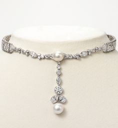 An Edwardian Platinum, Diamond and Natural Pearl Choker Necklace, Marcus & Co., Circa 1910. Designed as an openwork strap centring an articulated pendant set with two natural pearls, enhanced by two pear-shaped diamonds, and an old European-cut diamond, set throughout with marquise-shaped, single- and old European-cut diamonds, signed Marcus. #Marcus #Edwardian #choker