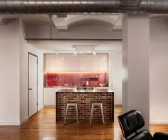 A steel and brick island within a loft  apartment.