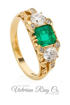 This three stone emerald and diamond engagement ring is a Victorian style half hoop ring. The centre stone is a bright green square-step cut emerald and in keeping with the era the two side diamonds are Victorian/Old-cut. The 18ct yellow gold band has been intricately carved. #halfhoopring #victorianstylering #alternativeengagementrings #emeraldring #emeraldanddiamond Victorian Engagement Rings, Diamond Engagement Rings, Emerald Diamond, Diamond Cuts, Scroll Pattern, Alternative Engagement Rings, Bright Green, Yellow Gold Rings, Gold Bands