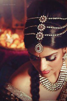 A unique hair piece (matha patti) for a bride who wants a high bun up do - love the simplicity of the plait and the vintage glamour of the traditional head piece - Indian bride - Indian wedding jewellery - Indian bridal hair and make up - dark gold eye shadow - red lips #thecrimsonbride