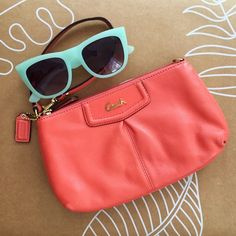 Coach coral wristlet EUC Used once and in excellent used condition. Perfect for your keys, phone, credit cards and more. There are a few very minor blemishes as seen in the photos and a slight discoloration on the inside of the strap from use. A coral/pinkish color. Authentic Coach. Coach Bags Clutches & Wristlets