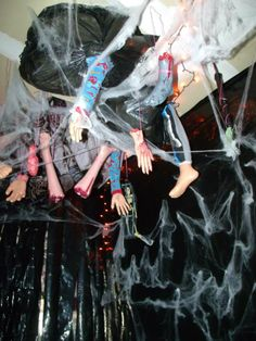Pic of our personal haunted garage: hanging body bag parts: SUPER CHEAP: dollar store hands or feet: taped to wrapping paper tube, cover tube with clothes of choice, stuff trash bag with wrapping paper and staple to ceiling. Takes less than 10 mins to make 1 bag - SERIOUSLY EASY WITH BIG EFFECT! Costs less than $4 per 2 you make!!!!  Candy G