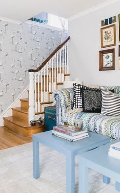 The entryway is a statement maker with the patterned wallpaper. The coffee tables are Ikea, and the trunks flanking the Anthropologie sofa are from a thrift store and an estate sale.