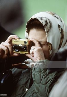 January 01, 1978, Queen Elizabeth II, a keen photographer, at Windsor Horse Show with her gold Rollei 35 camera in 1978 in England.