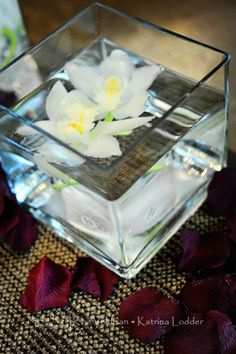 Maybe a square glass?  Floating Flower Centerpiece-Cheaper than buying flowers for a wedding!