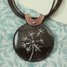 Beautiful enamel necklace with a whimsical dandelion. The dandelion is hand drawn in a traditional sgraffito technique which is drawing in enamel. Just like sgraffito in drawing or painting, it involves scratching through a layer of color to reveal the color below. It is suspended on a brown cotton multi strand cotton cord which has a sterling silver plate clasp. This entire piece is fired multiple times in the kiln.  The circle is 1 1/2 inches. The length is 18 inches. - Ilene Kay