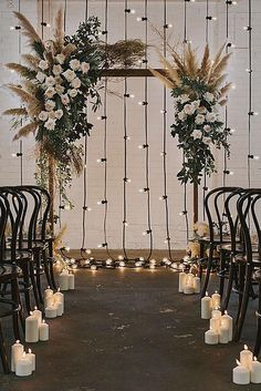 wedding backdrop ideas arch with flowers and feathers against the background of a glowing garland nouba via instagram