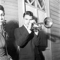 American singer and trumpet player Chet Baker (Chesney Henry Baker Jr.) playing in the backstage in a break from his concert. On the left, his wife Halima. 1957