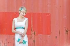 Brautkleid in Empire Linie mit Trägern und Carréeausschnitt und Knopfgürtel in Smaragd und Grün und schlichter Bestickung in Wellenlinien.