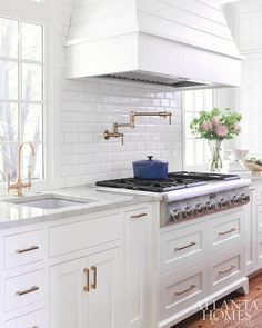 Kitchen Remodel Ideas A white shiplap French hood is mounted to mini beveled subway backsplash tiles above a stainless steel cooktop placed atop white shaker pot and pan drawers accented with brass pulls complementing a vintage brass wing arm pot filler. Kitchen Hoods, Kitchen Backsplash, Kitchen Cabinets, Subway Backsplash, Backsplash Ideas, Kitchen With Subway Tile, White Beveled Subway Tile, Inset Cabinets, Backsplash Design