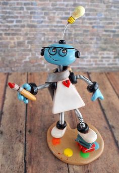 Artist Bot Robot Sculpture  Commission: requested details, square thin white dress body, light bulb antenna, round oval face, blue 'skin' body, wearing eyeglasses, a scarf wrapped around the neck, backpack with South African flag, holding a paint brush, standing on painter's palette and one foot raised on a stack of books. All with a rustic finish. Robot sculptures combining polymer clay, wire woven into coil springs, varnish and a little heart handmade by HerArtSheLoves…
