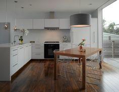 cuisine blanche avec parquet et table en bois et chaises en métal