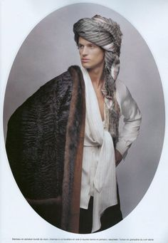 Manteau en astrakan borde de vison, chemise a col lavaliere en soie a rayures tennis et pantalon, Gaultier. Turban en grenadine du XVIII siecle (maybe)