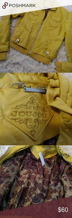 Faux Leather A brilliant mustard colored jacket that zips up front.  2 front oval pockets that snap.Beautiful lining with tags still on.  Shell is 💯 polyurethane, lining is 💯 polyester.  Leather on bottom back curls as also around neck. JouJou Jackets & Coats