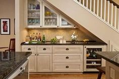 This bar area was crafted under the staircase for maximum functionality, even featuring an under-the-counter refrigerator. The space can also be used as additional cabinet storage for your unending supply of cups and plates.