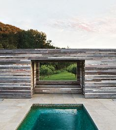 """Reclaimed Barn Wood Francis D'Haene, architect: """"I covered a poolhouse, including the walls, roof, and doors, in old barn wood from Kansas City, Missouri. It's already weathered from its previous life as barn siding. I left the wood as is, with bits of old paint showing."""" Elmwood Reclaimed Timber from elmwoodreclaimedtimber.com  at www.elledecor.com"""
