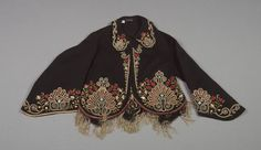 c1860s wool broadcloth jacket with silk embroidery and fringe and the remnants of a silk taffeta lining. Loop of braid at back neck for hanging. American. De Young Museum.
