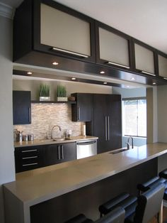 This kitchen provides plenty of storage with the addition of glass-front upper kitchen cabinets. A glass tile backsplash and stainless steel hardware complete the contemporary look.