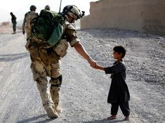 July 13, 2007: A Canadian soldier shakes hands with an Afghan boy during a joint patrol with Afghan National Army troops near Panjwaii village, Kandahar province, southern Afghanistan