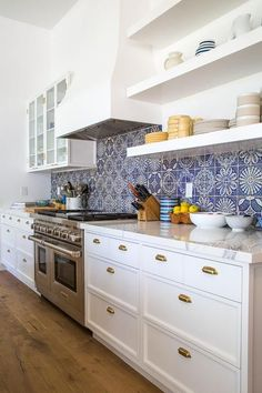 Dana Benson Construction - White kitchen cabinets adoring brass cup pulls and white marble countertops flank a stainless steel dual oven range positioned against blue mosaic backsplash tiles beneath a white French hook mounted between white floating shelves and glass front cabinets.