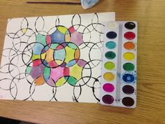 """Kaleidoscope Painting""  Paint the lid of a cup with black paint and use it to stamp overlapping circles.  Once it dries, paint inside each shape with a different color."
