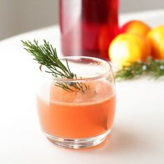 A glowy pink cocktail made with fresh clementines, cranberry juice, and vodka - garnished with a juniper sprig.