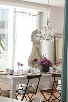 dining room    white farm house style table with great outside chairs inside, and romantic chandelier fun curtains... very shabby chic.
