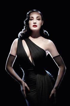 Burlesque star Dita Von Teese wearing black asymmetrical gown & gloves.