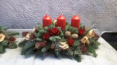 Red Christmas table centre with 3 red pillar candles, red roses and skimmia, cones, cinnamon, pine, fern and dried fruit slices. Christmas Flowers, Red Christmas, Christmas Wreaths, Christmas Arrangements, Table Centers, Dried Fruit, Fern, Pillar Candles, Red Roses