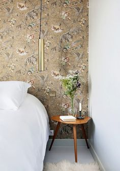 French hotel room with vintage floral wallpaper, white bedding a modern low-hanging gold pendant light