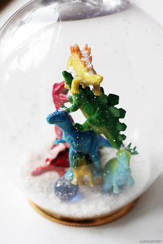 DIY dinosaur snow globe from toys, wine glasses, coasters and sugar. Tutorial by Alicia Sivertsson, 2013.