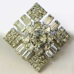 This is an older impressive diamante brooch with all clear diamante stones Square diamond shape with a raised center and round and baguette glass