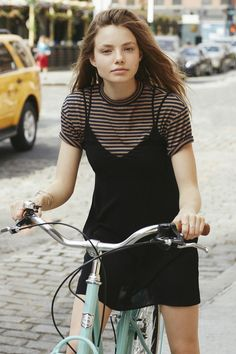 young woman with long hair, wearing a strappy black dress, over a striped cream and black t-shirt, riding a bike, 90s outfit ideas Indie Outfits, Hip Hop Outfits, Outfits Casual, Grunge Outfits, Summer Outfits, Fashion Guys, 90s Fashion, Fashion Outfits, Fashion Styles