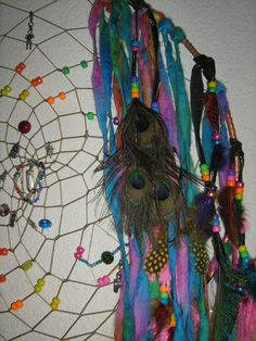 42 inches in length this beautiful Extra Large Mobile Dreamcatcher with Hand spun yarn that was spun on a spinning wheel and hand dyed to a Rainbow, with dazzling Rainbows of Crystal beads weaved throughout the center of the Dreamcatcher and tiny miniature birthstone baby charms.
