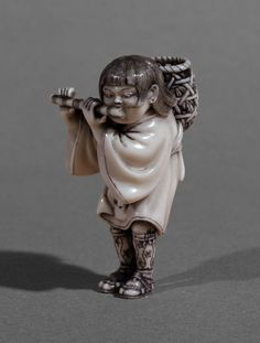 Netsuke of a grass-cutter's boy playing a flute, carved ivory, signed Hidemasa (秀正), Japan, 19th century.
