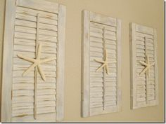 three shutters used as wall decoration with star fish mounted on them....great sea side look anyone can do....